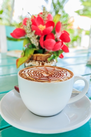 Cup of coffee with flower on wooden table photo