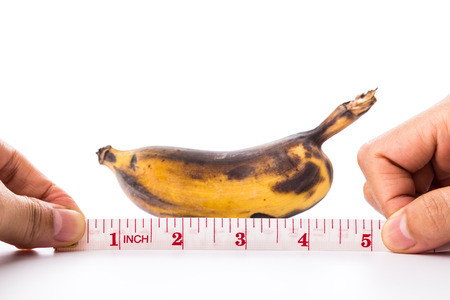 banana and measuring tape on white background