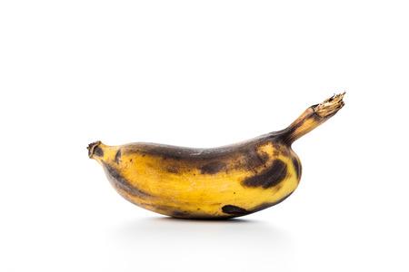 Black rotten banana on white background