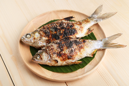 grilled fish on wooden plate
