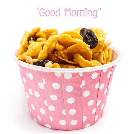 Breakfast : Caramel cornflake with currant in pink paper cup on white background