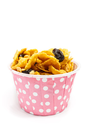 Caramel cornflake with currant in pink paper cup on white background Stock Photo