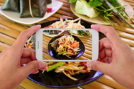 Woman taking a photo of thai food with smartphone