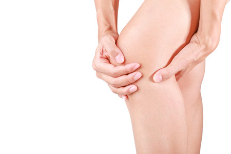 Knee pain.Female holding hand to spot of knee pain on white background.