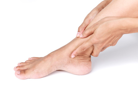 sprained joint: Ankle sprain.Female holding hand to spot of Ankle pain on white background. Stock Photo