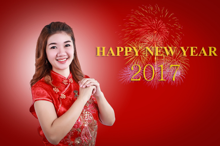 Happy new year 2017 and Chinese new year.Smile Chinese woman dress traditional cheongsam and introduce on red background. Stock Photo