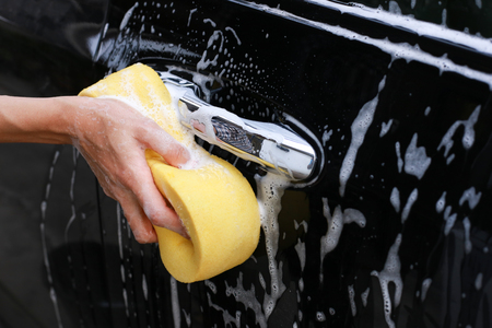 Washing car.Female hand with yellow sponge washing car Stock Photo