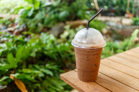 Ice coffee on a wooden table.Popular for thai people