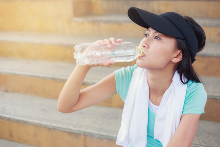 Beautiful fitness athlete woman drinking water after work out exercising