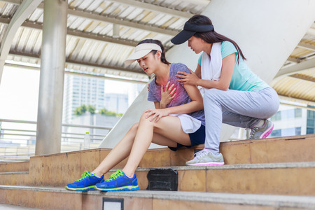 Sport girl try to help her friend who having symptomatic chest pain.Myocardial infarction Stock Photo