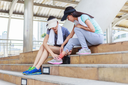 Ankle pain.Sport girl try to help her friend who having symptomatic ankle pain