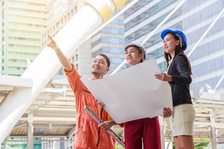 Engineer or Architect team and worker looking paper plans at construction site.