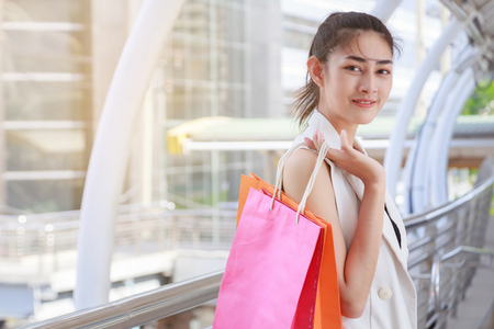 happiness, consumerism, sale and people concept - smiling young asian woman with shopping bags