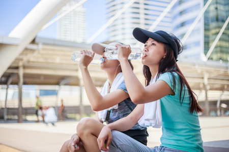 Beautiful young asian woman drinking water after training in city