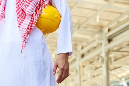 torso of arab engineer or worker hold in hand yellow helmet for workers security Фото со стока