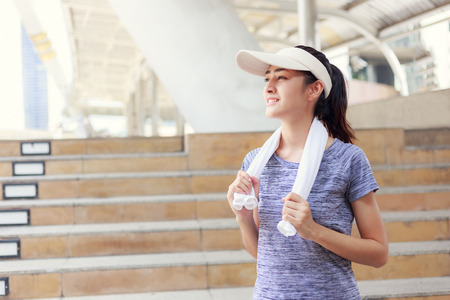 young  woman smiling  with a towel on her shoulder relaxing after jogging  in city