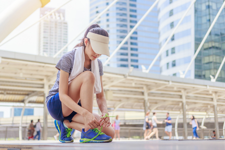 Beautiful girl tying shoe laces before running outdoors. Female sport fitness runner. Stock Photo