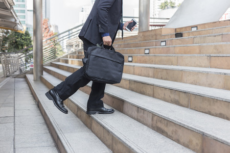businessman holding bag  while walking upward on the stair outdoor in city.go forward concepts. Stock Photo