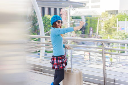 Young woman tourist with suitcases take a selfie at bangkok,Thailand