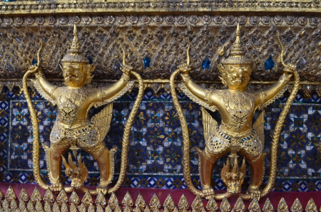 Small golden giant statues in front of the Emerald Buddha entrance Stock Photo
