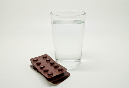 a pack of pills with a glass of water Stock Photo