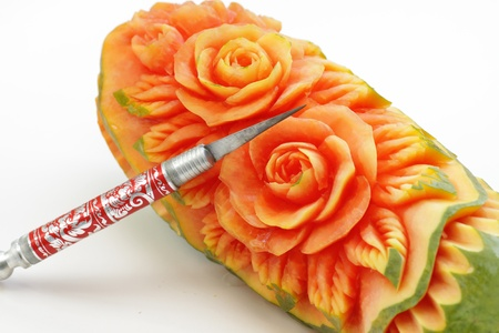 Carved papaya fruit and knife the art of Thailand 스톡 콘텐츠