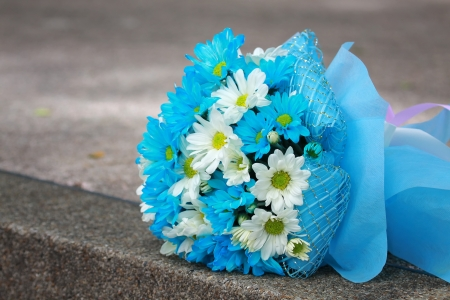 beautiful bouquet of bright blue and white flowers, on  table on green background photo