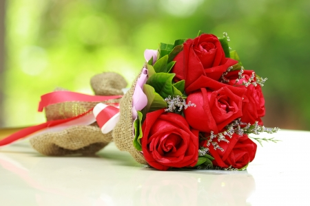 mixed flower bouquet: beautiful bouquet of bright red flowers, on  table on green background Stock Photo