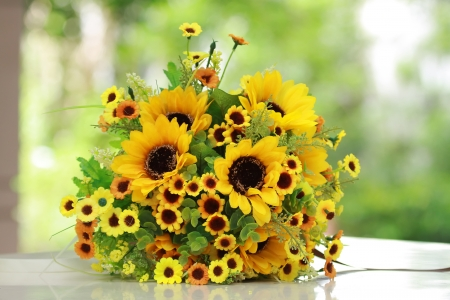 mixed flower bouquet: beautiful bouquet of bright yelloe flowers, on  table on green background