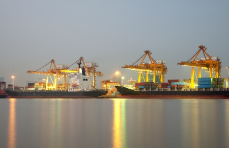 Container Cargo freight ship with working crane bridge in shipyard at dusk for Logistic Import Export  photo