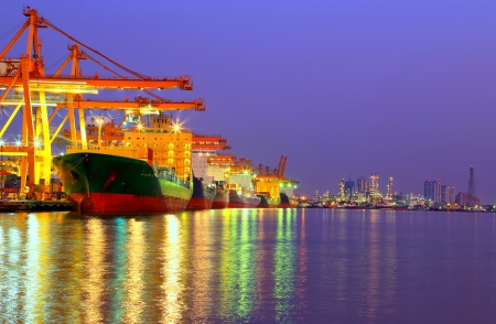 Industrial Container Cargo freight ship with working crane bridge in shipyard at dusk for Logistic Import Export with oil plant background