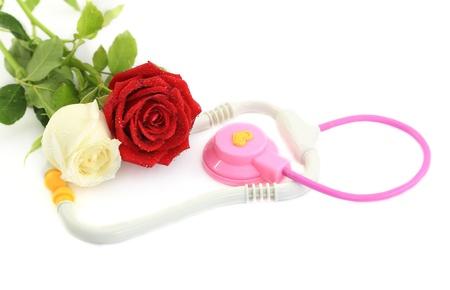 Medical stethoscope with rose on white background