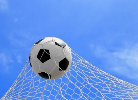 soccer ball in net on blue sky photo