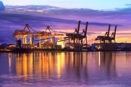 Industrial Container Cargo freight ship with working crane bridge in shipyard at dusk for Logistic Import Export background Zdjęcie Seryjne