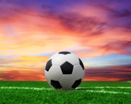 ballsport: football on green grass with beautiful sky