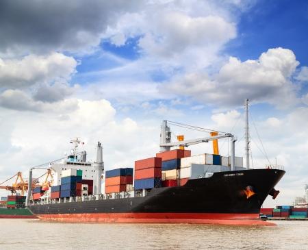 Cargo ship at the port outgoing with blue sky Foto de archivo