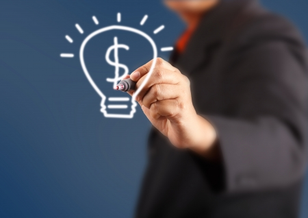 businessman hand with a pen drawing light bulb inside is dollars photo