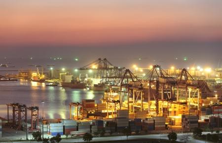 물류 가져 오기 내보내기 배경에 대해 황혼 조선소에서 크레인 다리 작업 산업용 컨테이너화물 운송 선박
