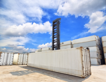 forklift handling the reefer container box at dockyard photo