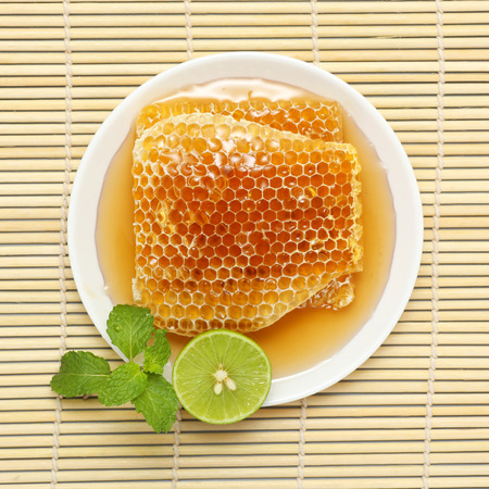 Sweet honeycombs in dish with lemon and mint on bamboo mat photo