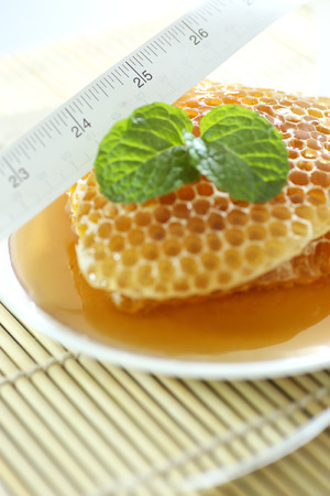 Close up sweet honeycombs with mint leaf  photo