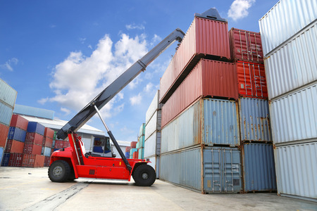 forklift handling the container box at dockyard with blue sky photo
