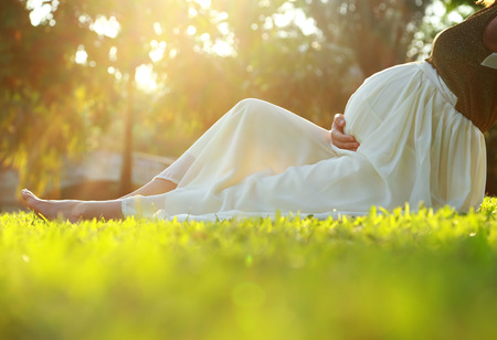 Pregnant woman sitting on the grass floor in the morning at park photo