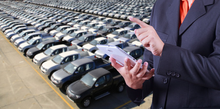 Business man counting motor vehicles in storage yard photo