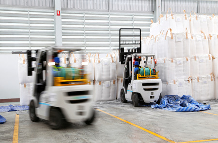 worker driving a forklift loader in warehouse with load jumbo bag  photo