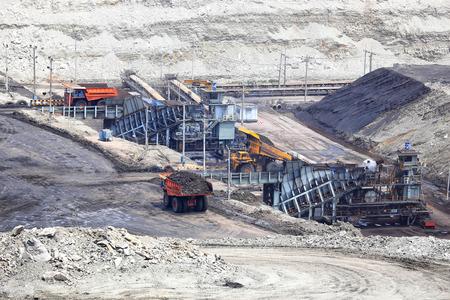 browncoal: heavy construction tipper trucks dump coal to the conveyor at coal mine