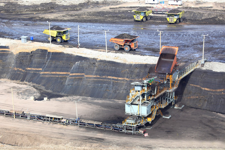 browncoal: heavy construction tipper trucks dump coal to the conveyor at coal mine