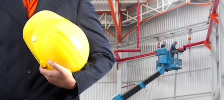 conection: construction safety concept with worker on crane mobile conection red tube systems at warehouse background