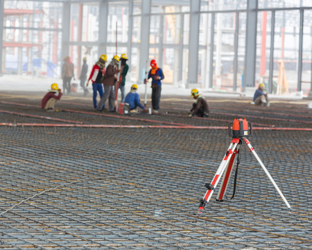 geodesist: Automatic Level with Adjustable Leg Tripod and Aluminum Rod. Automatic level handles at warehouse building with worker working background