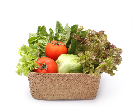 Fresh vegetables in wicker basket isolated on white photo